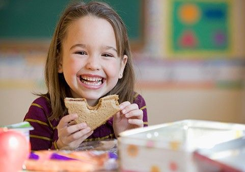 a child eating sandwitch and smiling